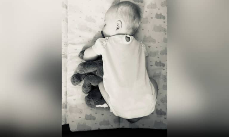 Baby curled up in crib, black-and-white photo