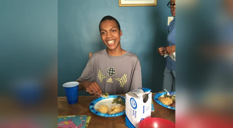 Smiling teen boy at table