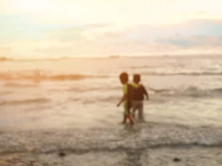 Young kids playing in ocean, blurred photo