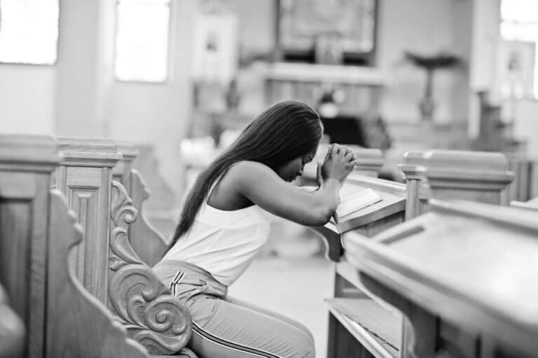 Woman praying in church pew