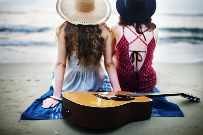 friends on beach with guitar