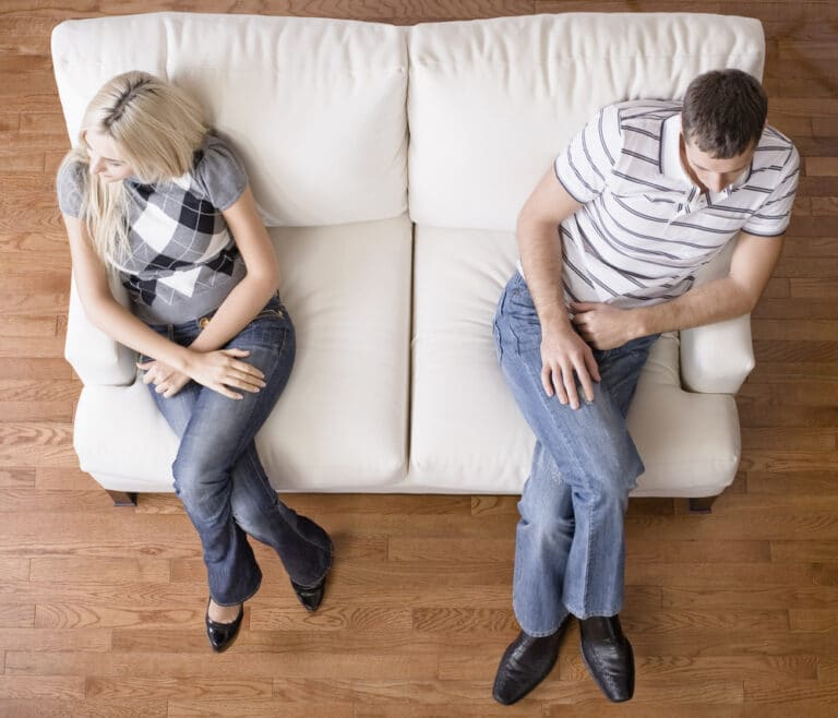 Couple sitting on far ends of couch