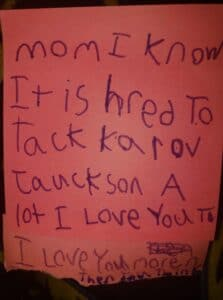 Sticky note with child's handwriting, color photo