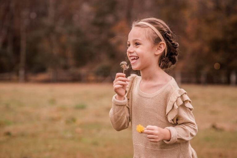 Little girl holding flower and smiling, color photo