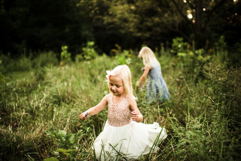 Two little girls in a field of grass, color photo