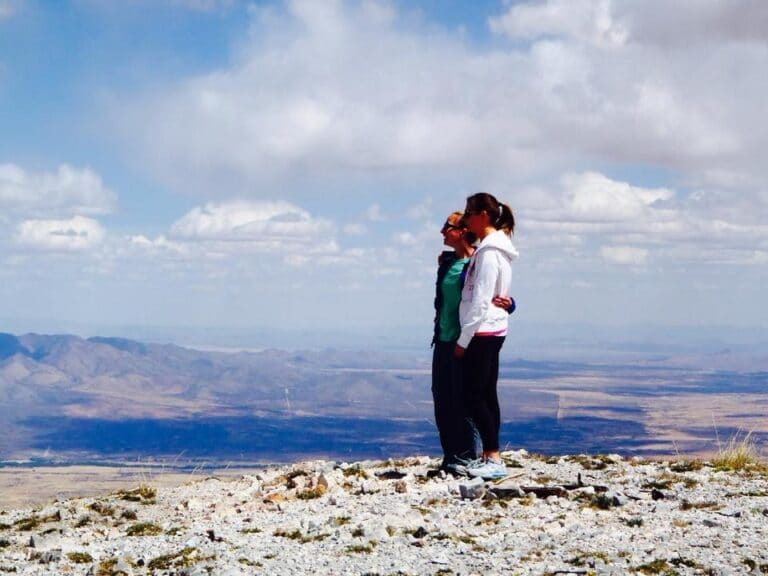 Two people standing on a hill, color photo