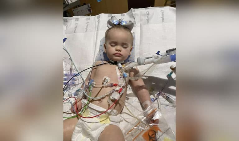 Child attached to tubes in hospital bed