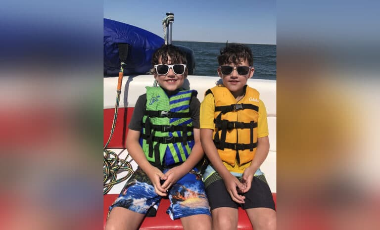 Twin boys in lifejackets on boat, color photo