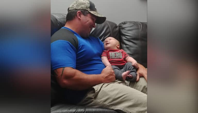 Daddy holding infant son, color photo