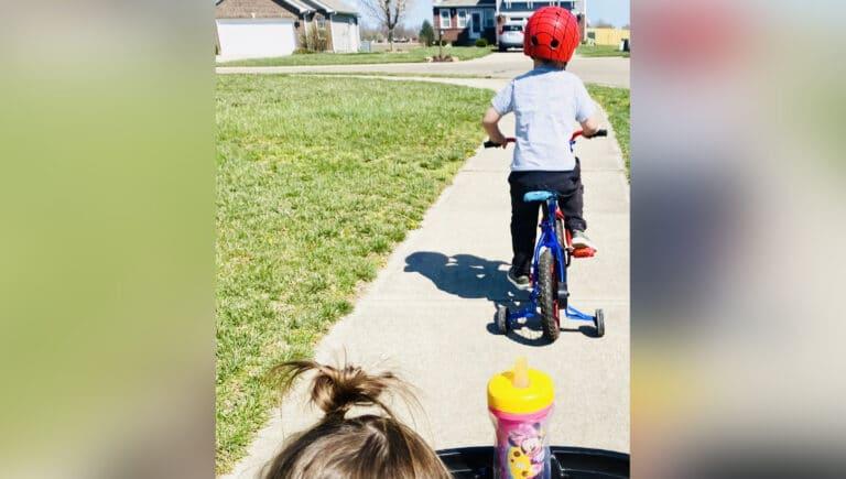Little boy riding bike down sidewalk, color photo