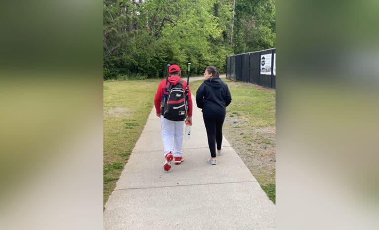 Teen siblings walking down sidewalk, color photo