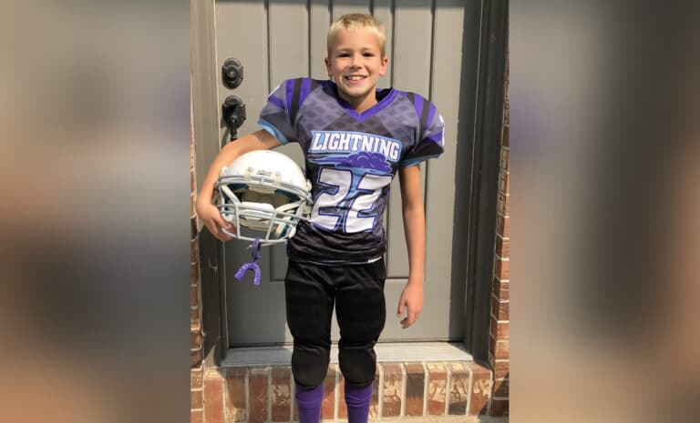 Young boy in football uniform, color photo