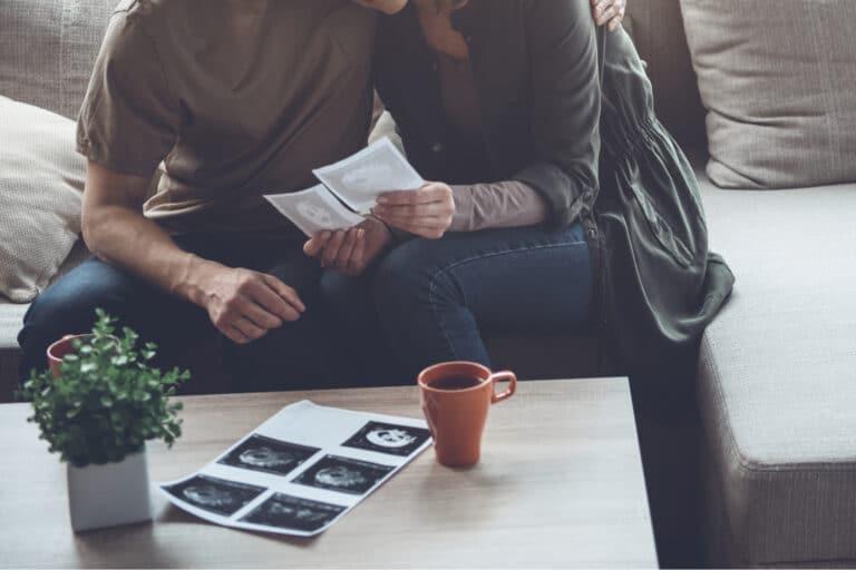 Couple holding ultrasound photos