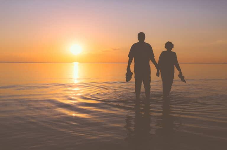Couple walking on beach at sunset