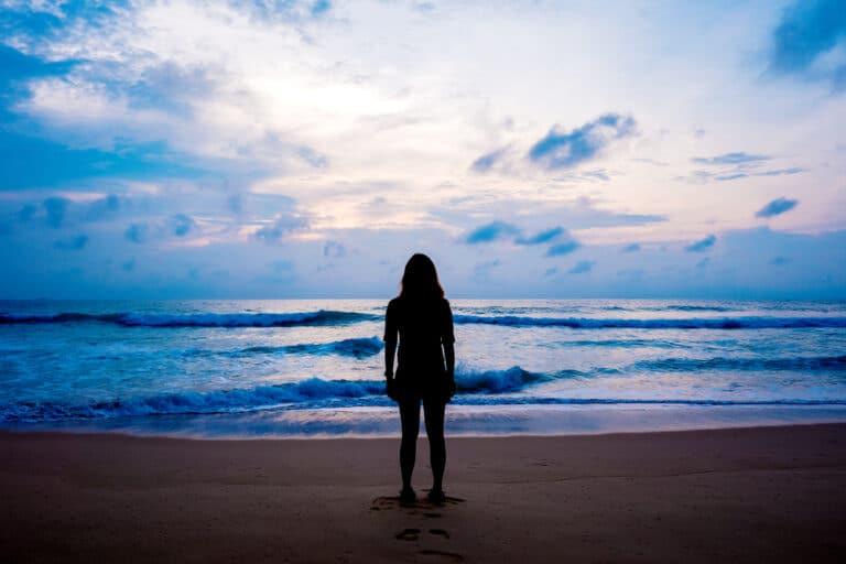 Woman standing on beach alone
