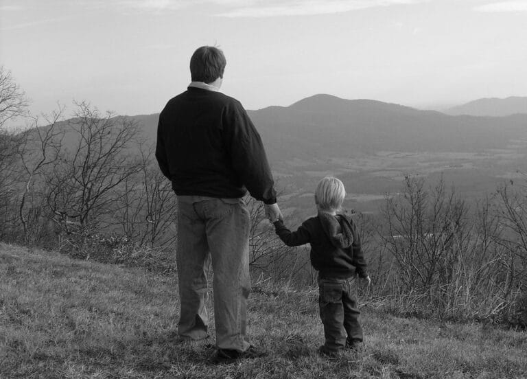 Dad holding child's hand, black-and-white photo