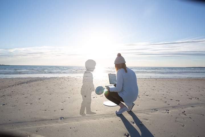 Mother on beach with photo-shopped image of son's shadow, color photo