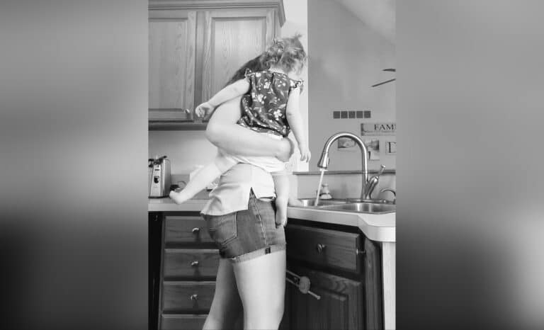 Woman with child on her hip standing at kitchen sink, black-and-white photo