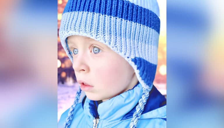 Blue-eyed boy in blue jacket and stocking cap, color photo