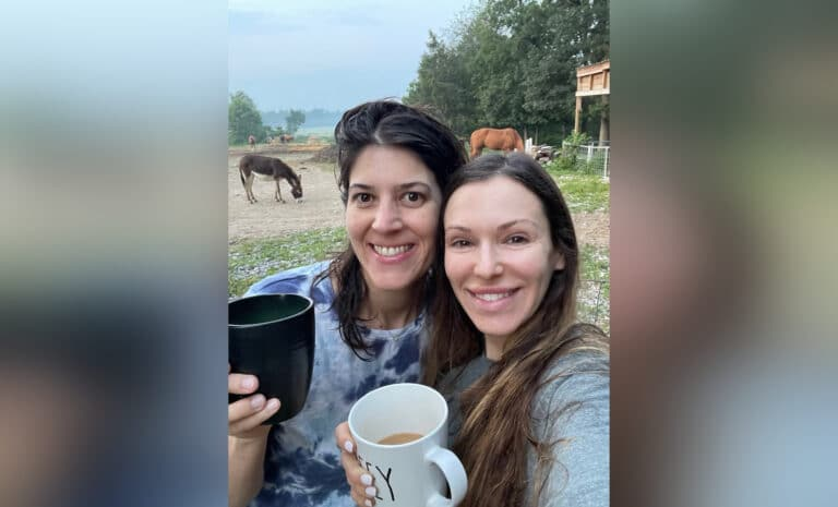 Two women smiling, holding coffee cups, color photo