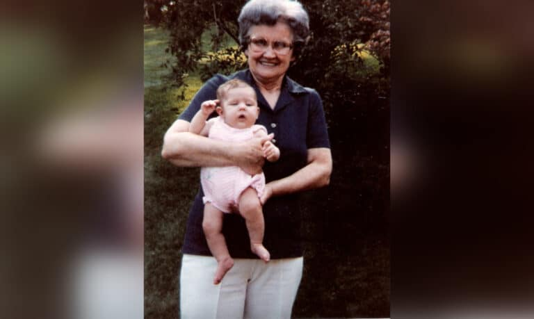 Grandmother holding infant, color photo