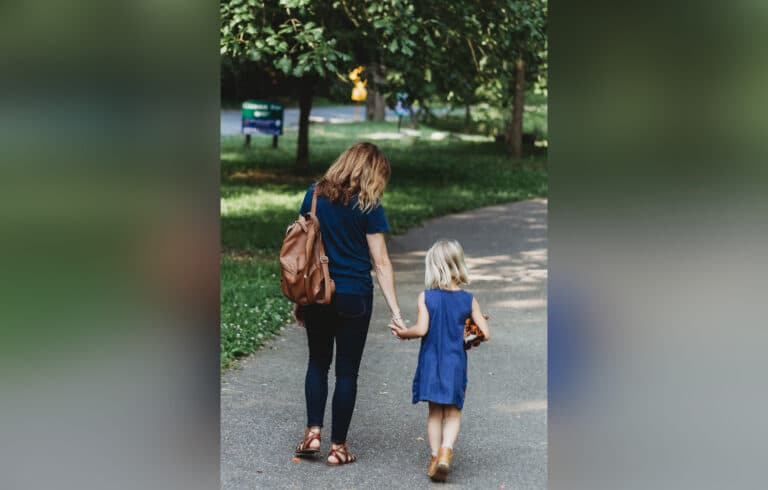 Woman holding daughter's hand while walking, color photo