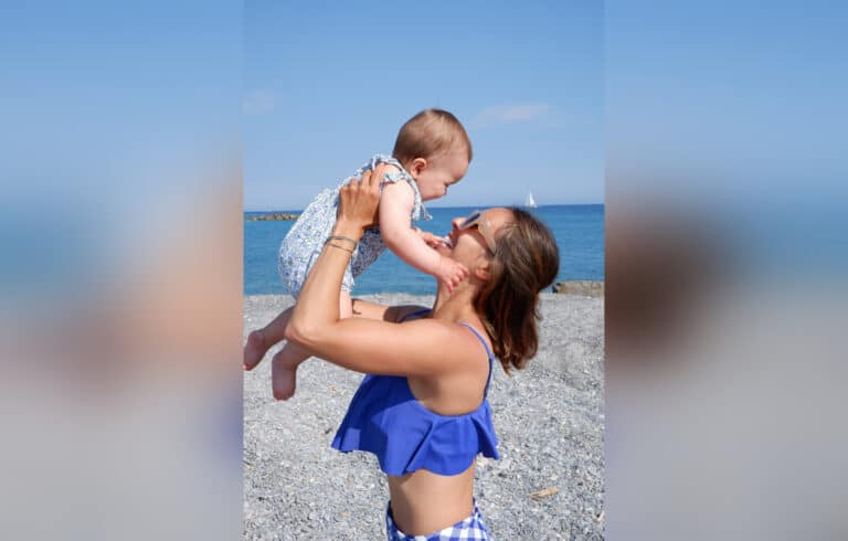 Woman holding baby on the beach, color photo