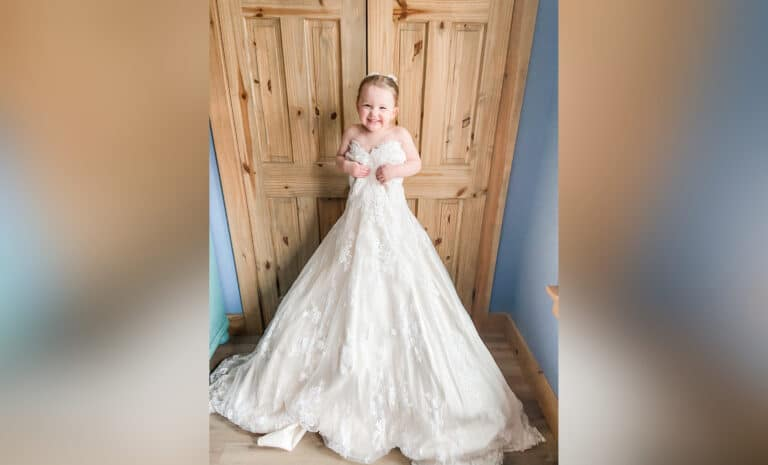Little girl in her mother's wedding dress, color photo