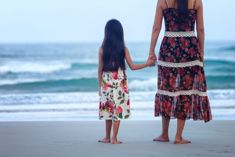 Mother and child standing by ocean