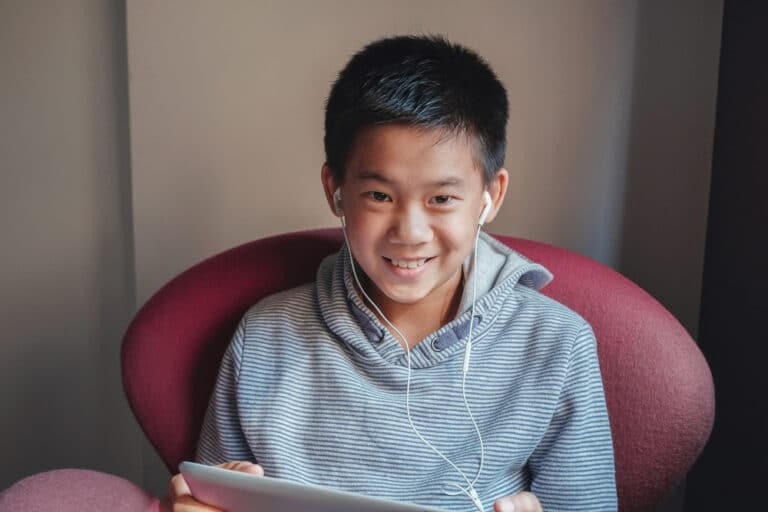 Tween boy using tablet and smiling