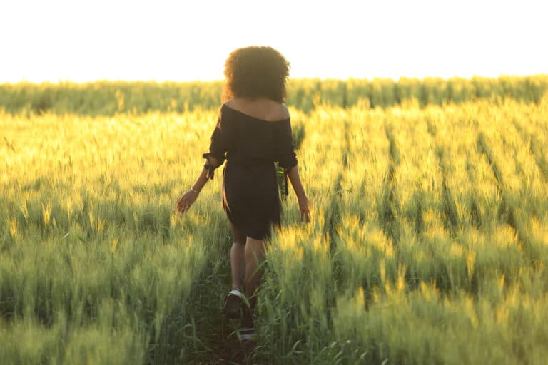 Woman walking in field at sunset