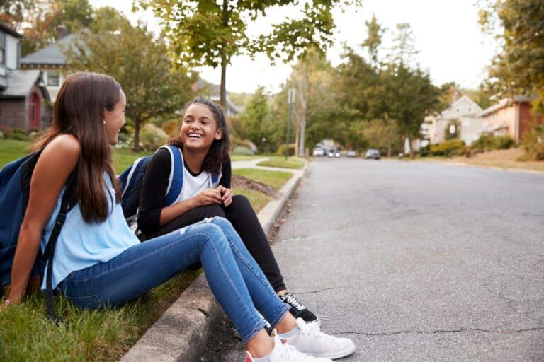 Two teen girls talk outside
