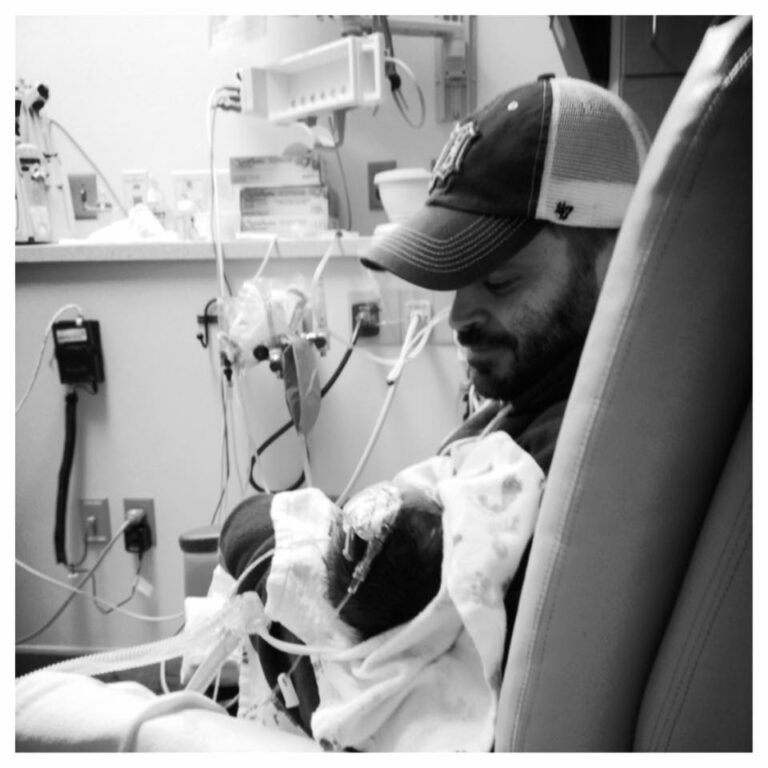 Man holding baby in NICU