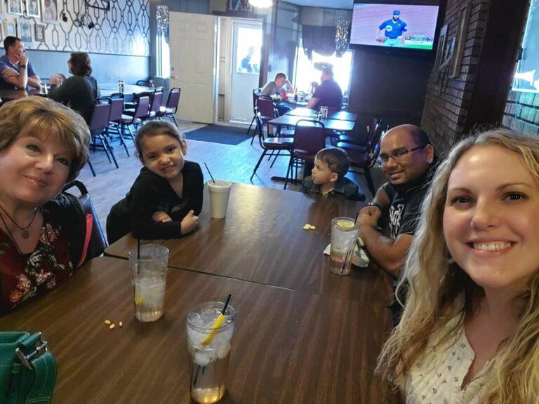 Parents, kids, and grandma at a restaurant, color photo