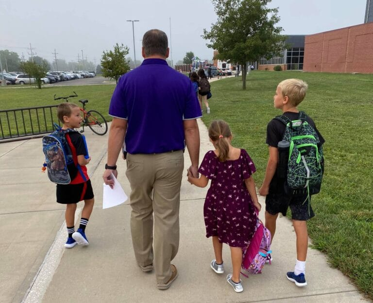 Kids walking with dad to school