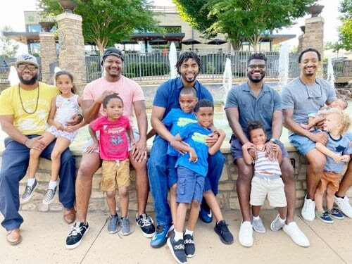 Group of black fathers with their children, color photo