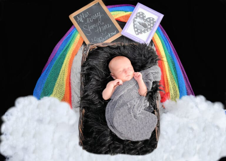 Baby lying on blanket surrounded by a rainbow, color photo