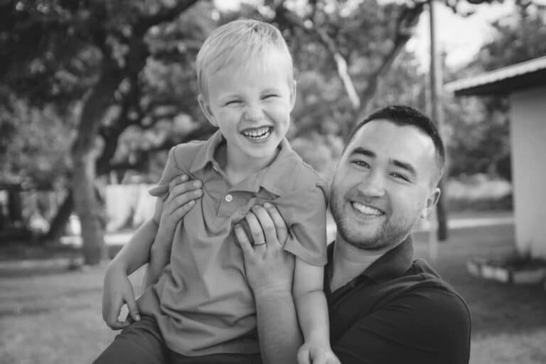 Father holding young boy, black-and-white phot