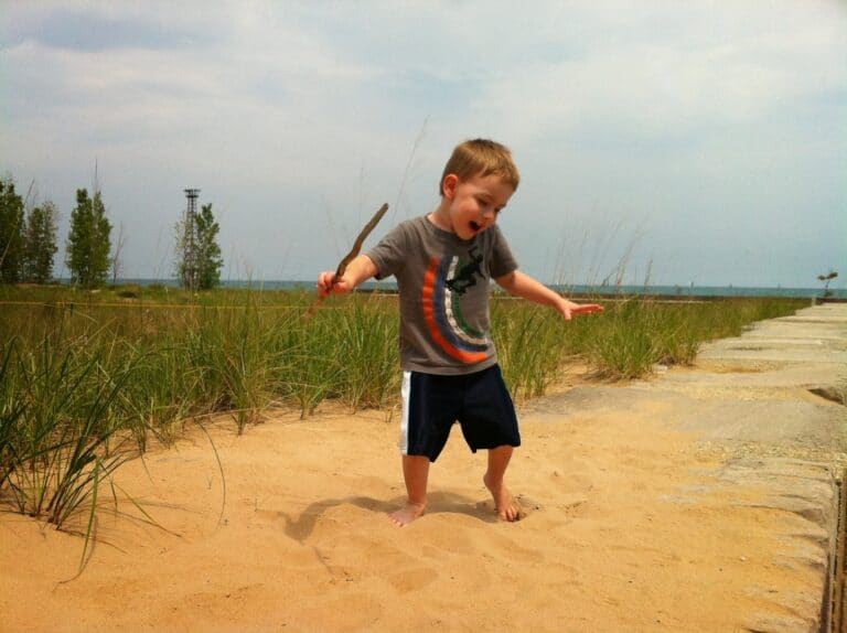 Young boy dancing in sand, color photo