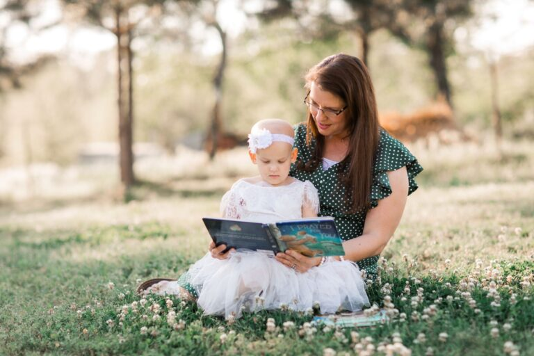 Mother holding daughter on lap while reading, color photo