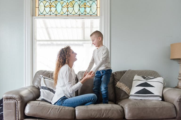Woman sitting on couch with son, color photo