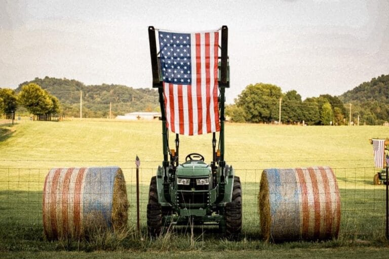 Tractor with American flag between bales, color photo