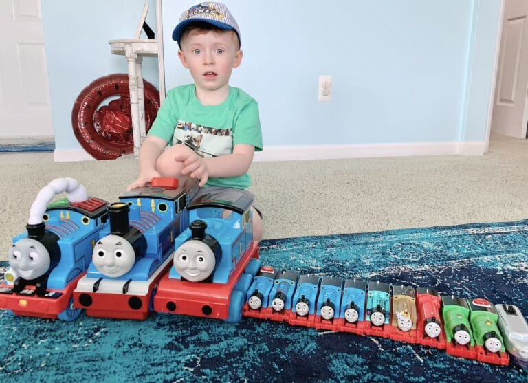 Little boy with toy trains lined up in front of him, color photo