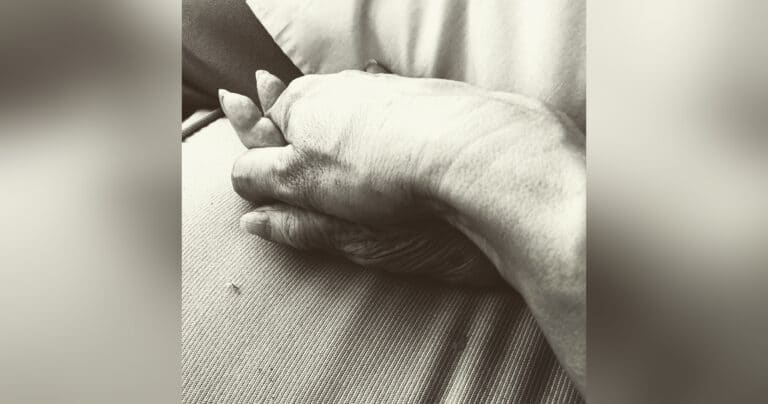 Woman holding mother's hand, black-and-white photo