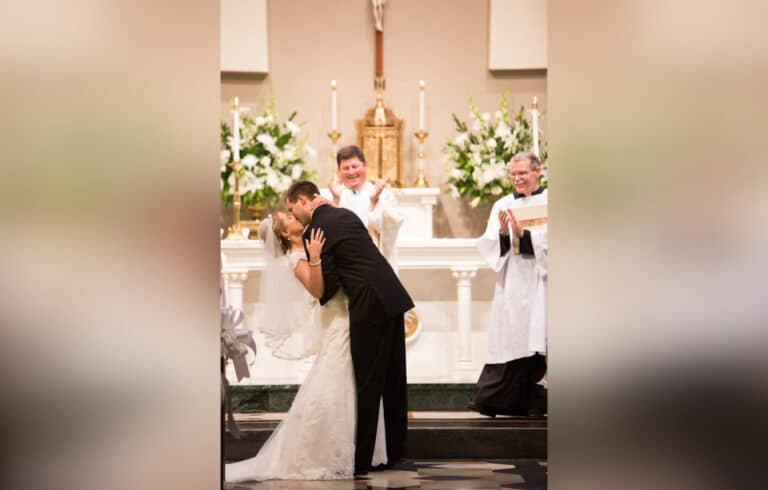 Groom kissing bride in church, color photo