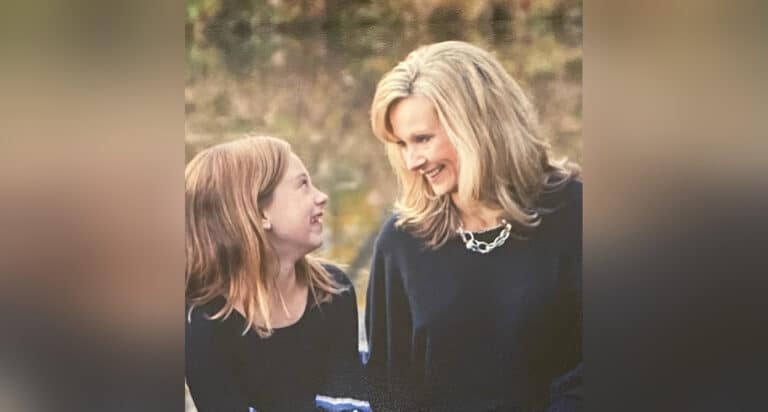 Mother and daughter smiling at each other, color photo