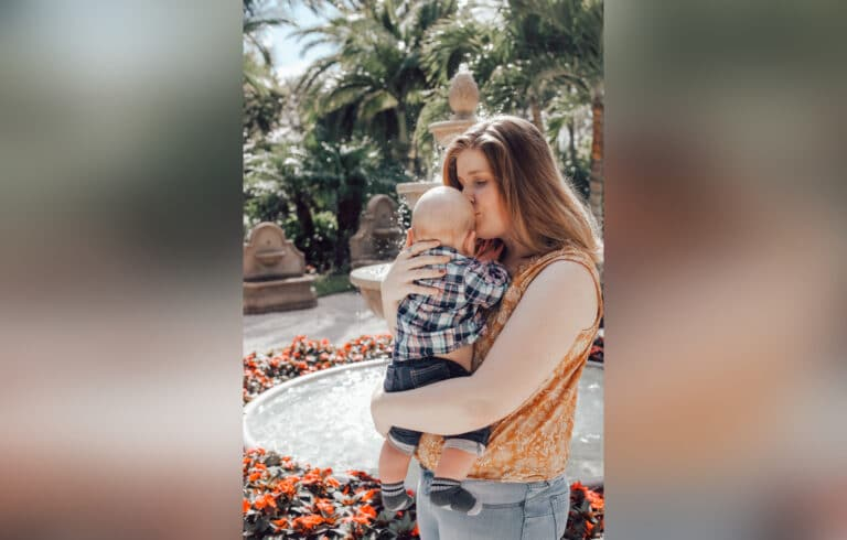Mother kissing baby, color photo