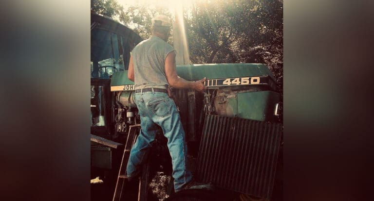 Man standing next to tractor, color photo