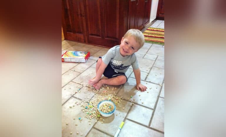 Little boy on kitchen floor with spilled cereal, color photo