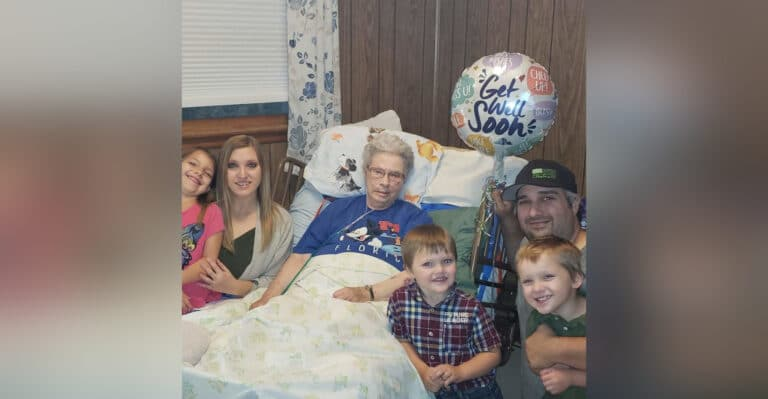 Family surrounding woman in hospital bed, color photo